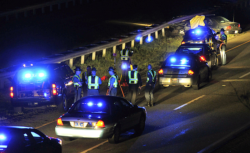 Maine State Police troopers converge at the scene of a crash just off Exit 63 on Interstate 95 late Monday night following a shooting and police chase. After the car visible at the top was stopped by spike mats, the driver, Nathaniel Gordon, killed himself, police say. He earlier had killed his wife, Sarah Gordon, in Winslow, according to police.