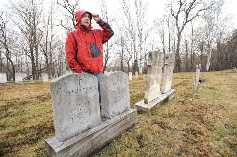 """Ben Godsoe of the High Peaks Alliance land trust is leading an effort to build a 45-mile trail between Strong and Oquossoc that marks the places where Cornelia """"Fly Rod"""" Crosby fished and worked. Here, he stands beside Crosby's grave at the start of the trail in Strong."""