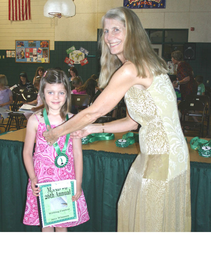 Carol Weeks, SAD 6 assistant superintendent, presents kindergarten student Amelia Zimmel with a ribbon in the district's 26th annual writing contest at an honorary tea held for winners at Bonny Eagle Middle School in Buxton.