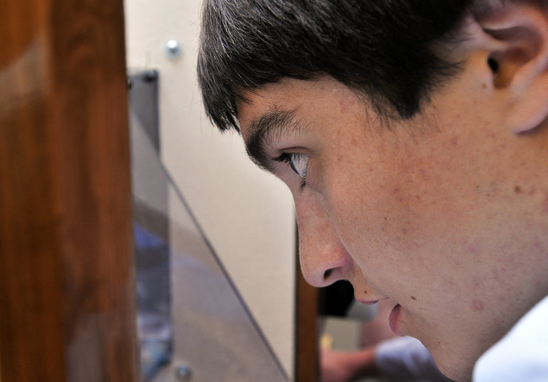 Evan LaMarre, a senior, peers into the test chamber of the wind tunnel created by eight Freeport students.