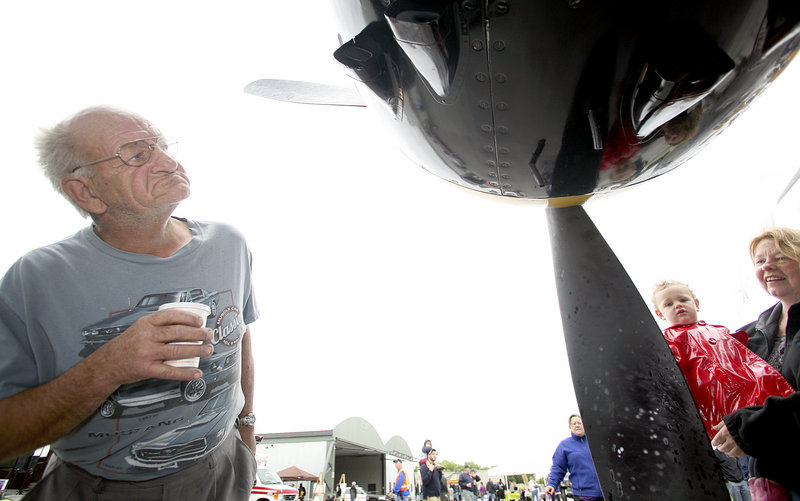 Wayne Young of South Portland inspects a North American RB-25 Mitchell Bomber as Beth Lunt of Old Orchard Beach holds Ivy Diou, 1, of Portland so she can touch a propeller.