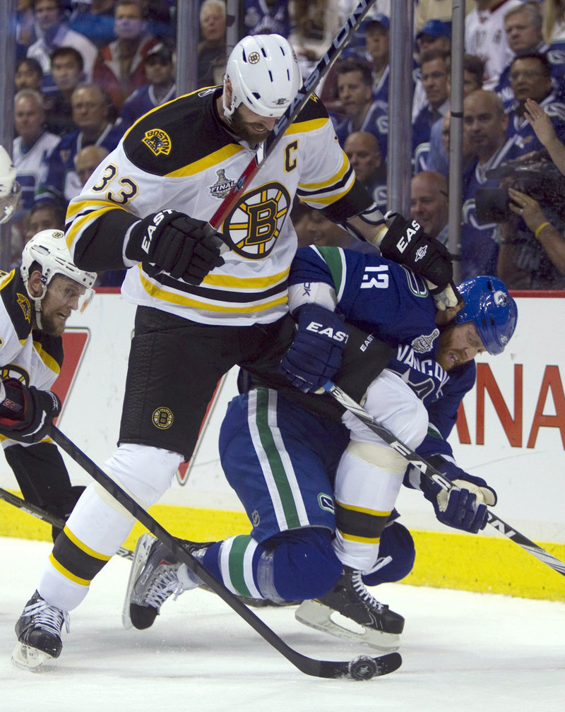 Zdeno Chara of the Boston Bruins takes down Raffi Torres of the Vancouver Canucks in the first period. Chara had a much more important task after the game – accepting the Stanley Cup as the captain of the team.