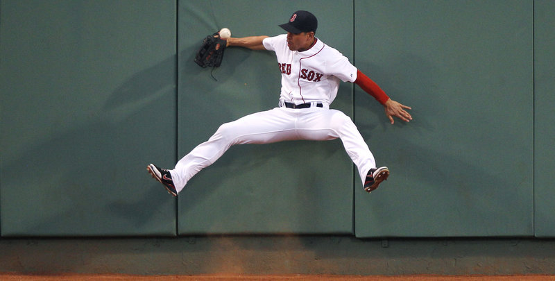 Left fielder Darnell McDonald of the Boston Red Sox slams into the wall while attempting to make the catch on a triple hit by Jesus Guzman of the San Diego Padres in the fourth inning Monday night. The Padres kept the game tight until the Red Sox used a 10-run inning to salt it away.