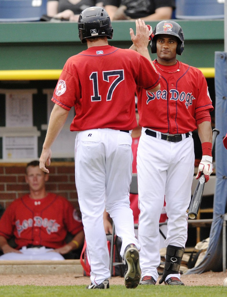Mitch Dening, left, is greeted by Jorge Padron after scoring the Sea Dogs' run in the first-game loss.