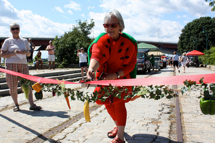 Dressed as a watermelon, South Portland Mayor Rosemarie De Angelis cuts the ribbon at the opening of the first South Portland Farmers Market.