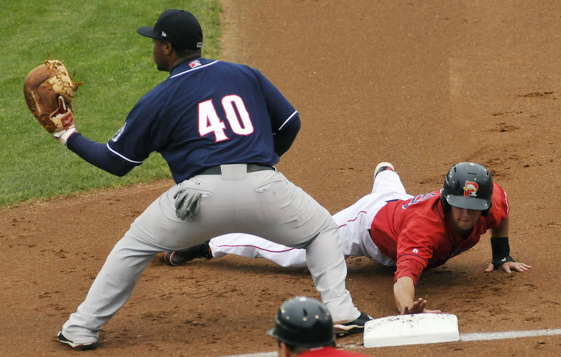Alex Hassan of the Portland Sea Dogs dives back to first base Sunday night as Mike McDade of the New Hampshire Fisher Cats takes a pickoff throw during the Sea Dogs 5-2 victory at a sold-out Hadlock Field.