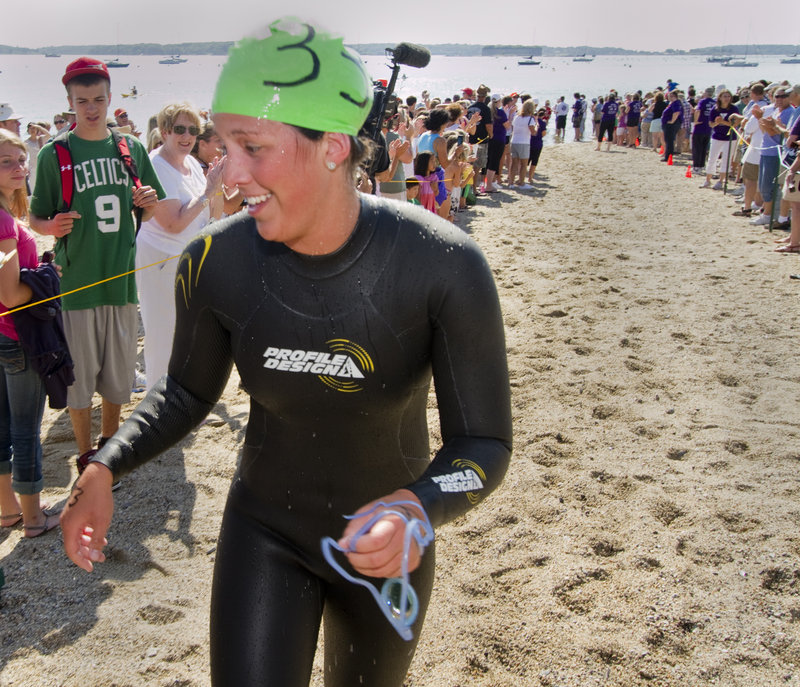 Kristen Desrosiers, 20, of Gorham scampers onto dry land Saturday after winning the women s division of the Peaks to Portland for the second straight year. She was the 20th overall finisher in a field of 279 swimmers.