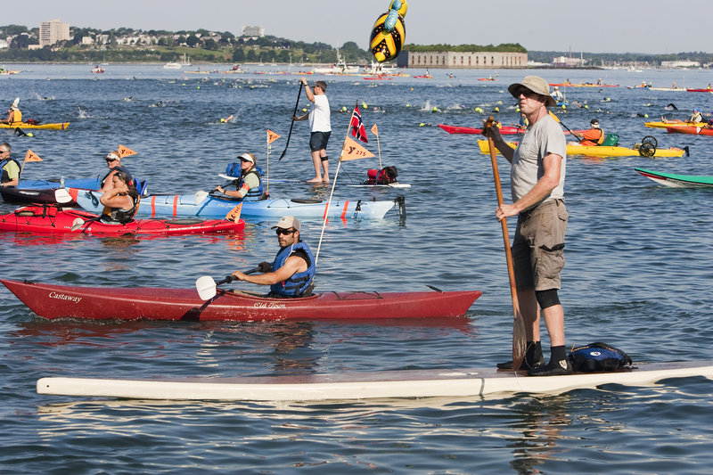 The kayakers and paddleboard escorts, including a Peaks Island summer resident, Steve B. King, standing in foreground, wait to accompany the swimmers Saturday as the race to Portland is about to begin.