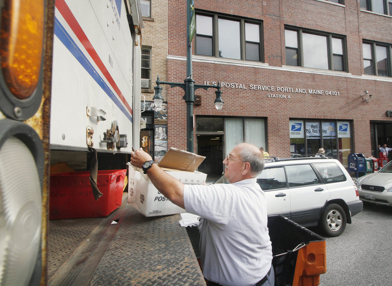 A postal worker loads a truck at the Station A Post Office on Congress Street in Portland on Tuesday. The branch was also listed for closure last year, but public response kept it open.