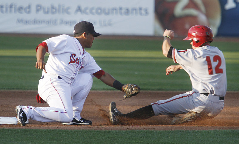 Heiker Meneses of the Portland Sea Dogs prepares to slap a tag on Brock Holt of the Altoona Curve, who was caught attempting to steal second base Thursday night in the first inning of Altoona's 7-4 victory at Hadlock Field.