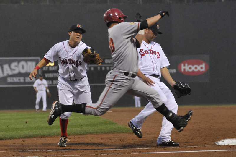 Sea Dogs first baseman Jon Hee, left, attempts to reach Altoona's Yunesky Sanchez as pitcher Charlie Haeger pulls up to avoid a collision. Sanchez beat the tag and was safe at first, but Haeger won his debut with the Sea Dogs.