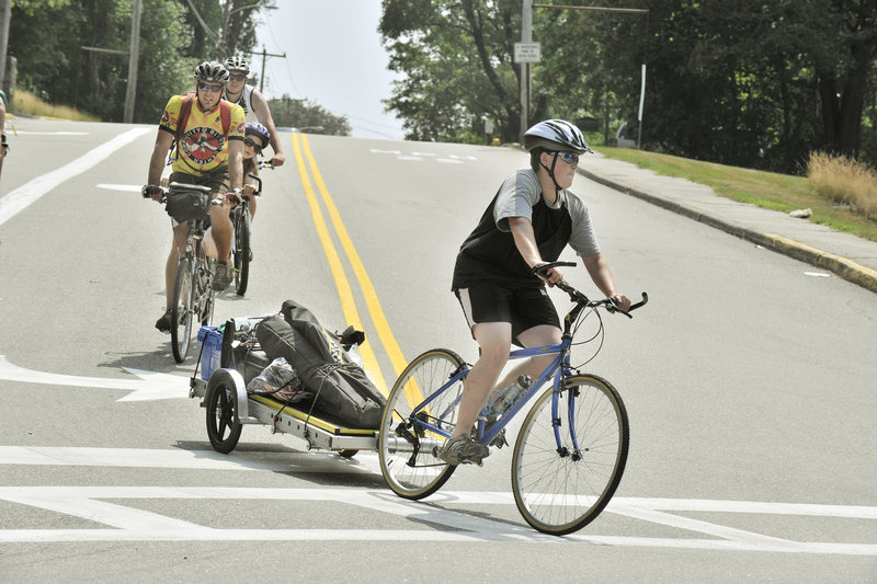 Matt Perkins hauls a small trailer of bike repair tools from the Community Bicycle Center to Rotary Park in Biddeford while a group of CBC staffers follows him.