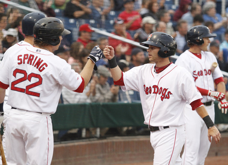 Ryan Khoury of the Portland Sea Dogs is greeted by teammates Tuesday night after scoring a first-inning run on a triple by Mark Wagner at Hadlock Field. Portland went on to a 9-2 victory against the Akron Aeros.