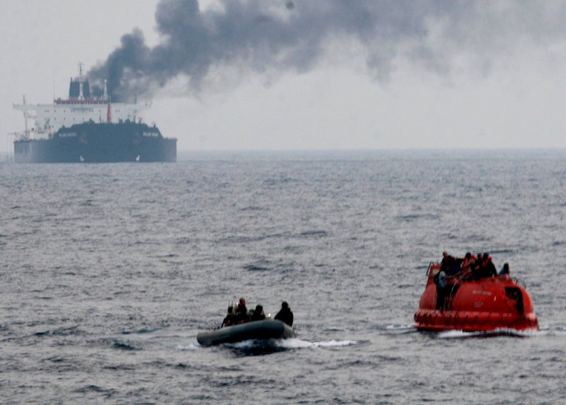 Sailors from the USS Philippine Sea approach a lifeboat, right, to rescue crew members from the Brillante Virtuoso last month in the Gulf of Aden. The tanker is burning in the background.