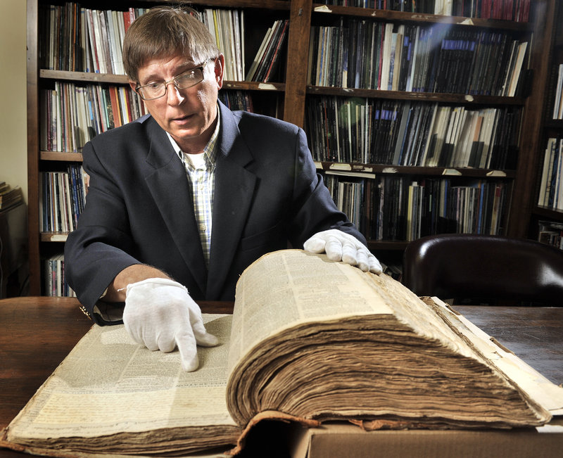 Bill Gage leafs through the pages of an 18th-century newspaper that will be auctioned off later this month. The Bangor Historical Society owns the documents.