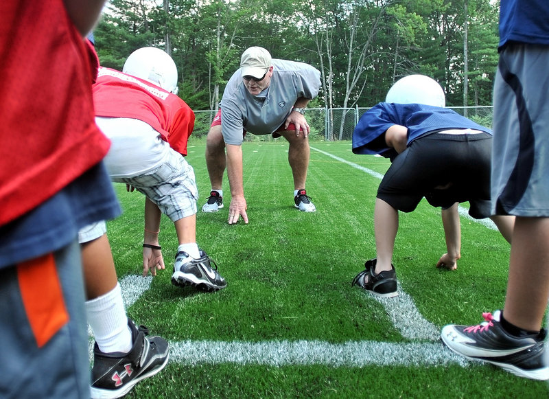 Marty Lyons, a former defensive lineman with the New York Jets in the NFL, demonstrates the proper stance Friday to youngsters at the Camp Tracy Youth Football Camp in Oakland.