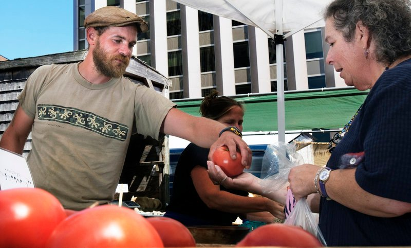 Chris Cavendish of Fishbowl Farms in Bowdoinham hands a tomato to a customer at the farmers market last week.