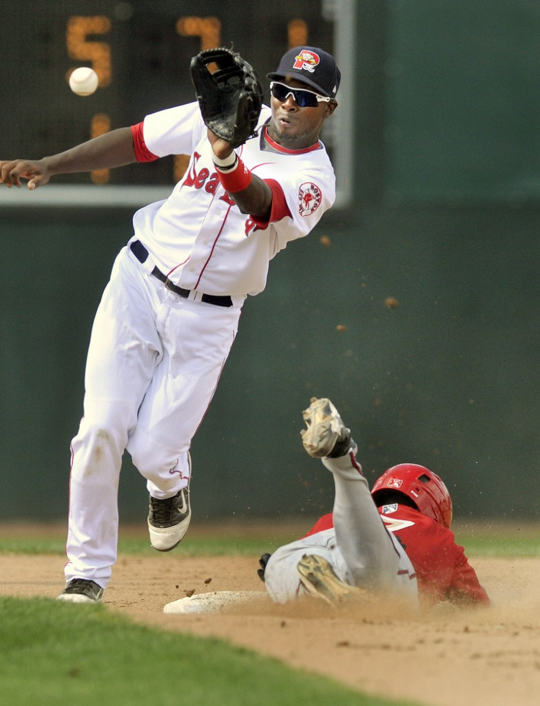 Second baseman Oscar Tejeda of the Sea Dogs pulls in an errant throw Wednesday as Archie Gilbert of the Harrisburg Senators steals a base in the eighth inning of Harrisburg's 9-3 win. Portland has lost seven straight.
