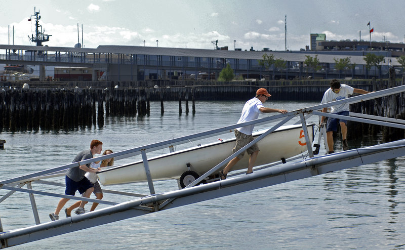 From left, Dylan Bruce, Jessica McGreehan, Doug Baker, and Kyle T. Randall, all of Sail Maine, remove one of Sail Maine's boats from the water on Friday in preparation for Hurricane Irene.