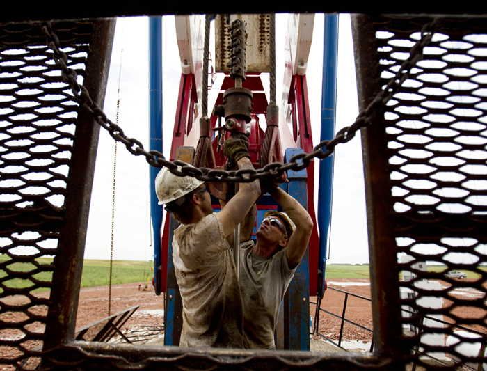 Austin Mitchell, left, and Ryan Lehto, work on an oil derrick outside of Williston, N.D. With what many are calling the largest oil boom in recent North American history, temporary housing for the huge influx of workers, known as