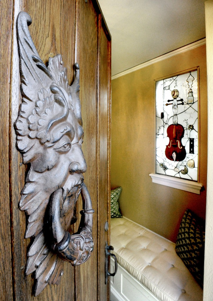 In the home's grand foyer, a piece of art by Laura Fuller of Fuller Glass in Portland hangs in a window catching light. It's stained glass imbedded with found objects, including antique bottles and a door lock and key, as well as the body of a violin.