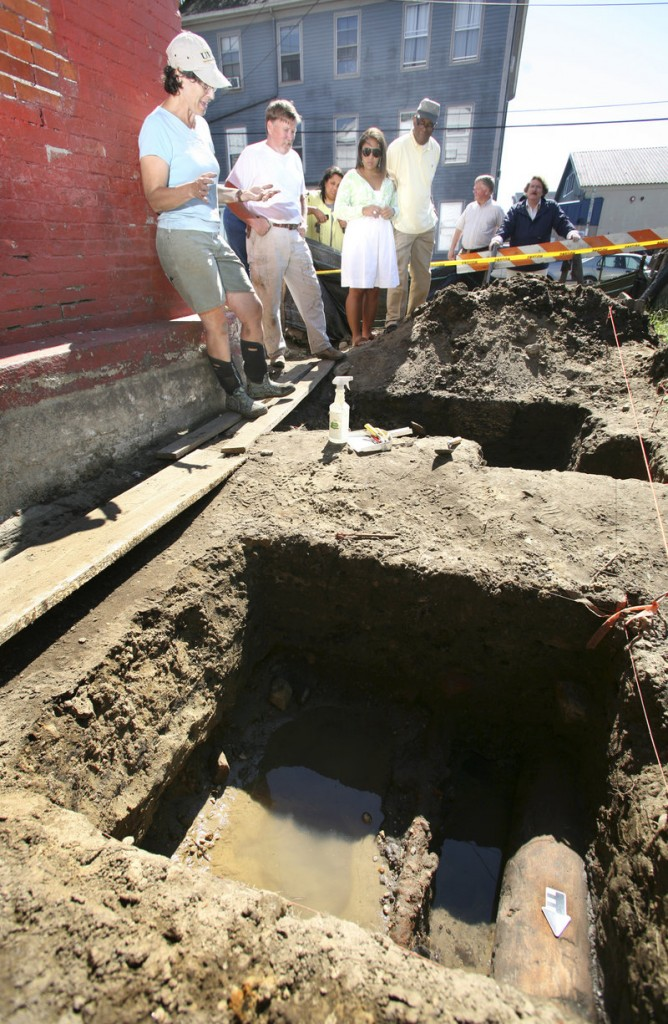 Archeologist Martha Pinello, far left, discusses the excavation at the historic Abyssinian Meeting House on Newbury Street where workers discovered early wooden underground water pipes that likely serviced area homes as well as the former Grandtrunk Railroad station in the mid-1800s.