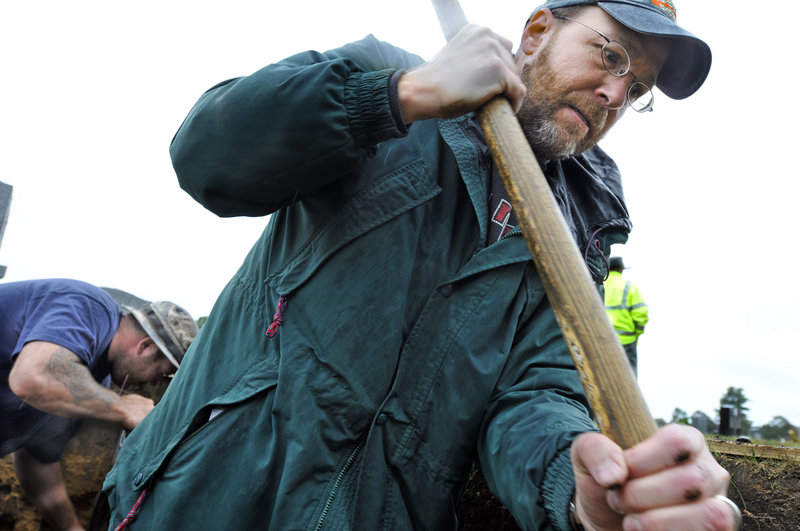 Ray Routhier digs a grave at Forest City Cemetery with the help of Portland Public Services laborer Chris Peterson.