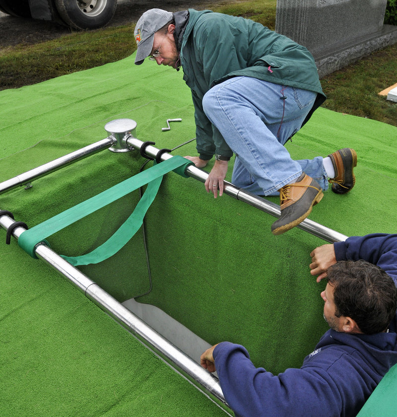 Ray Routhier climbs into a grave at Forest City Cemetery to help Portland Public Services foreman Larry Goodson clean the vault and prepare for a burial. The cemetery is owned by the city of Portland but is located in South Portland.
