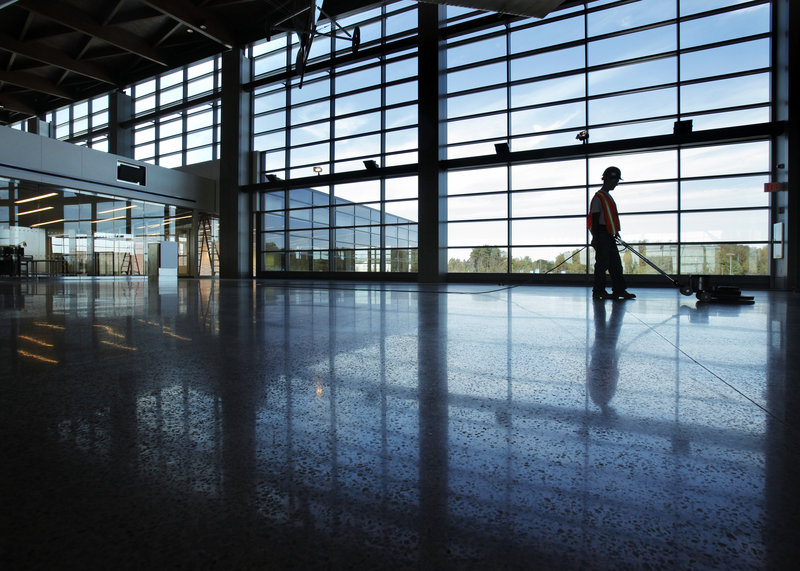 Ed Polinsky runs a floor polisher inside the new terminal at the Portland International Jetport. The terminal aims to blend Maine aesthetics with urban amenities. The public can visit on Saturday.