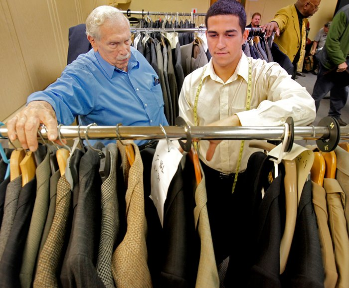 Aaron Dalpe, right, looks for a suit coat for John Corsa during the National Suit Drive at the Career Center in Portland on Tuesday.
