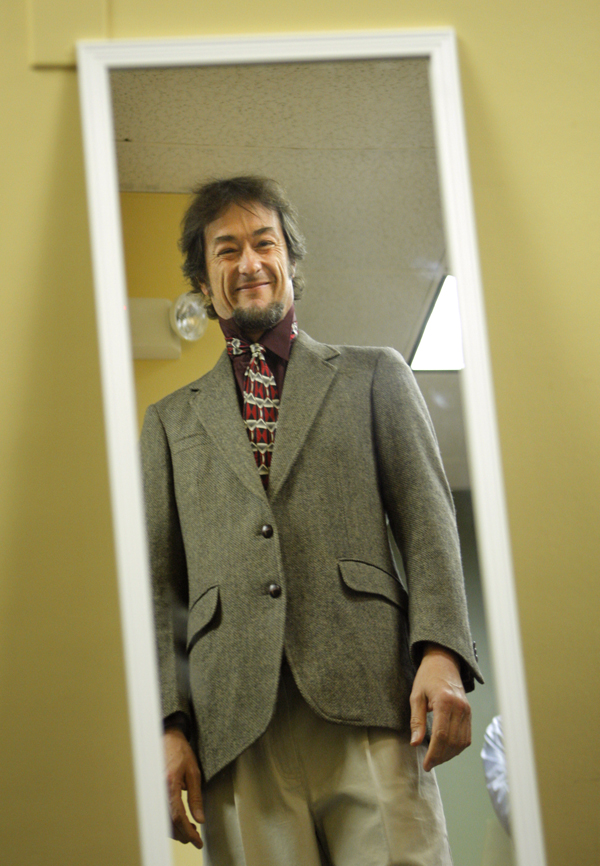 Matt Young checks out a suit in the mirror at the Career Center in Portland Tuesday. Young, a Portland musician, is seeking full-time work at an environmental nonprofit. He went home with a tweed jacket, slacks and tie.