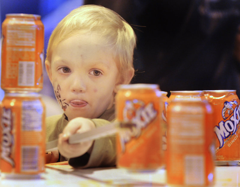 Jeremiah Lawrence, 4, of South Paris concentrates on stacking weighted Moxie cans in a game in the children's area of the annual festival.