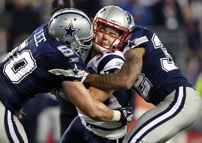 Danny Woodhead of the Patriots takes a hit from Dallas' Sean Lee, left, and Orlando Sandrick.
