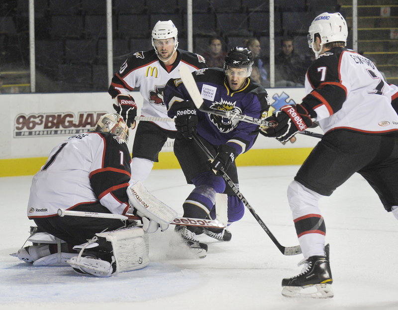 Justin Pogge of the Portland Pirates covers the puck after stopping a shot by Dwight King of Manchester.