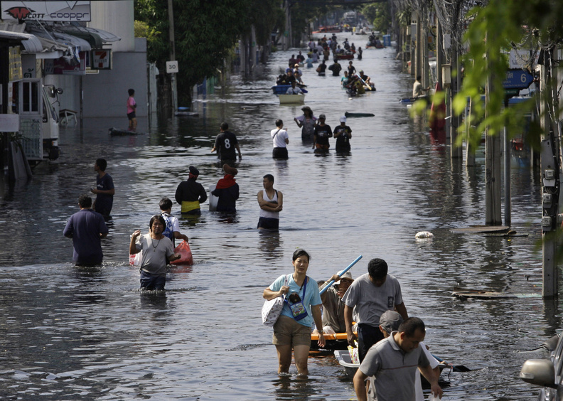 Thai residents carry their belongings as they move to higher ground Monday in flood-plagued Bangkok. The country has suffered its worst flooding in five decades, triggered by unusually heavy monsoon rains that began in July. A draft report by climate scientists warns that weather extremes will intensify as global warming worsens.