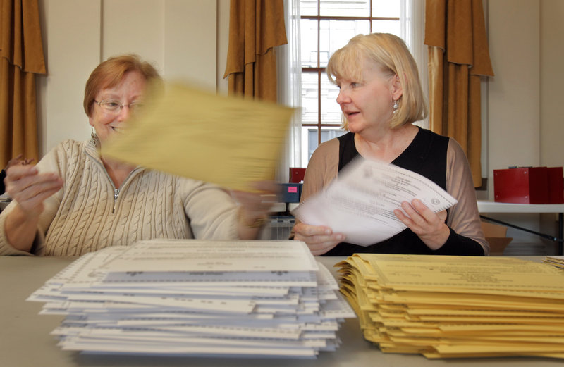 Elizabeth Boynton, left, and Teresa Bunn separate state and municipal absentee ballots Monday in the State of Maine Room at Portland City Hall. Boynton is a volunteer and Bunn is a vital records clerk for the city of Portland. Similar scenes played out around the state Monday.