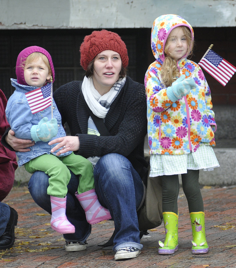 Clara, 2, left, and Willa Stefanski, 3, of Falmouth watch Portland's Veterans Day parade along with their nanny, Melissa Anderson.