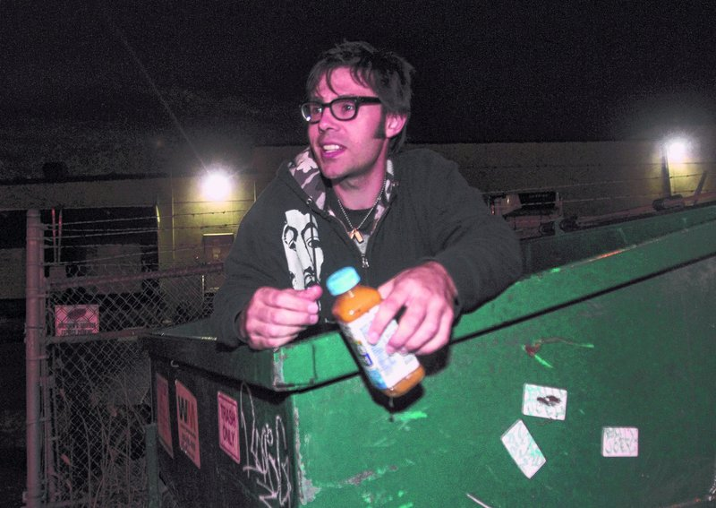 David Giles searches a Dumpster for discarded food as he researches his thesis on perceptions on edible food and why people discard something that may be safe to eat.