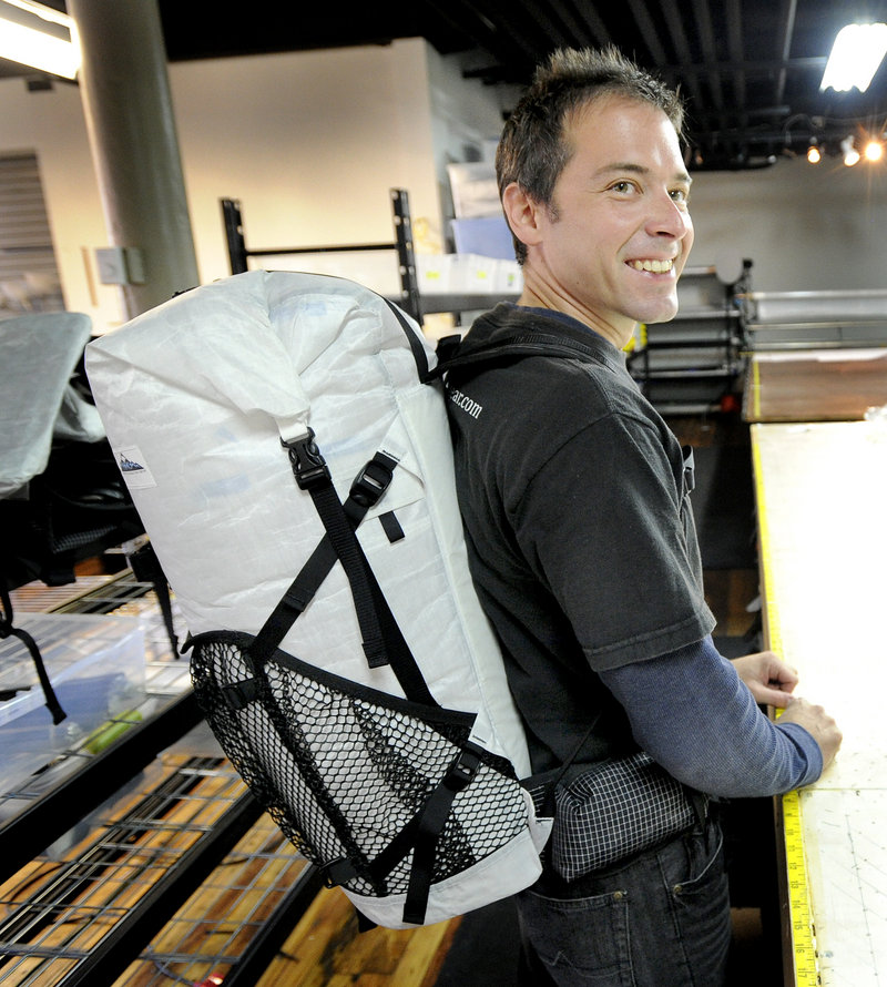 Mike St. Pierre, at his new business in Biddeford, models one of his backpacks.