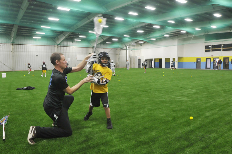 Deke Andrew works with Sean Dilworth, 9, of Falmouth during a lacrosse practice at the newly opened Riverside Athletic Center in Portland. The facility will cater to athletes passionate enough about one sport to want to play it year-round.