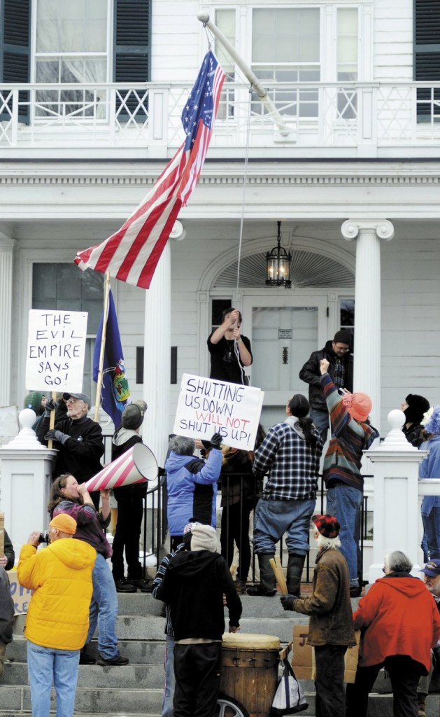 Occupy Augusta protesters hoist a flag embroidered with 99%, as well as an American flag, Sunday at the Blaine House.