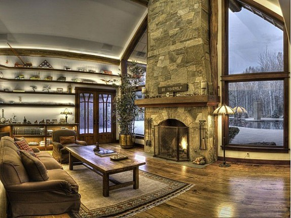 Actor Bruce Willis' Idaho home is marked by rustic stone and wood details, including two fireplaces in the living room area.