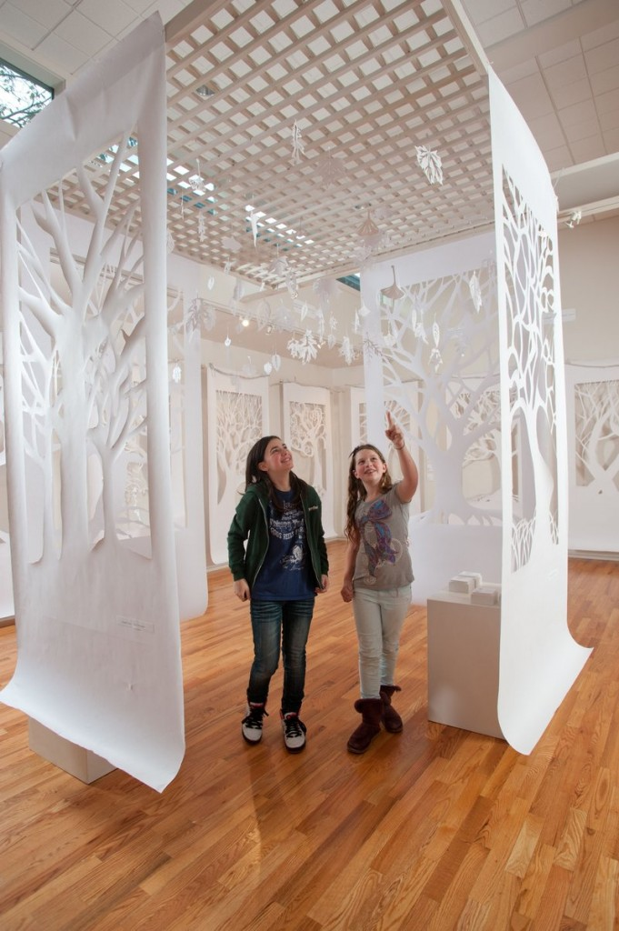 """Fifth-graders Meredith Connor and Annabel Huber admire """"Arboretum,"""" created by Waynflete School eighth-graders and hanging in the school's Art Gallery."""