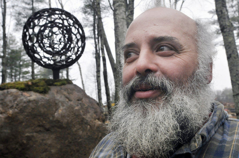"""Jay Sawyer suspended a spheroid created by Dave McLaughlin inside one of his own making for """"Late Collaboration,"""" which stands in a sculpture garden on Sawyer's property in Warren. Sawyer vows to carry forward McLaughlin's vision for heavy-metal art."""