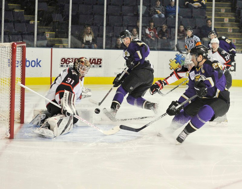 Curtis McElhinney, the goalie for the Portland Pirates, turns away a shot by Marc-Andre Cliche of the Manchester Monarchs, right, in the first period of the Monarchs' 2-1 victory Wednesday night at the Cumberland County Civic Center. Cliche is a former Lewiston Maineiac.