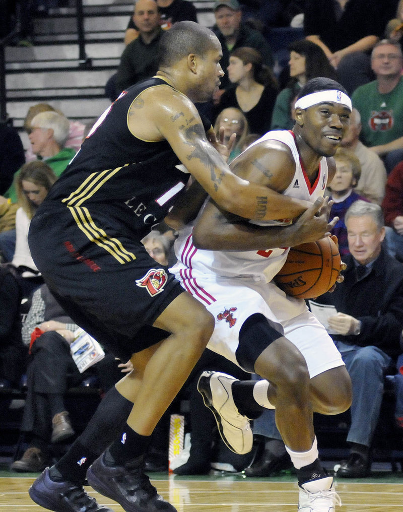 Paul Harris, right, of the Red Claws keeps possession of the ball Saturday night while fouled by Kyle Spain of the Erie BayHawks. Erie won 109-105 at the Portland Expo.