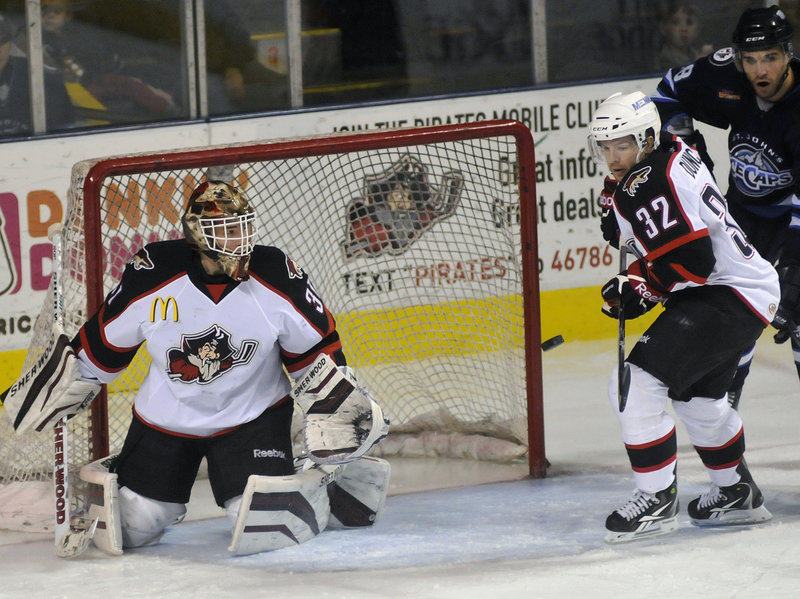 Pirates goalie Curtis McElhinney and forward Ryan Duncan watch the puck pass in front of the net during Portland's 5-2 loss Sunday to the St. John's IceCaps.