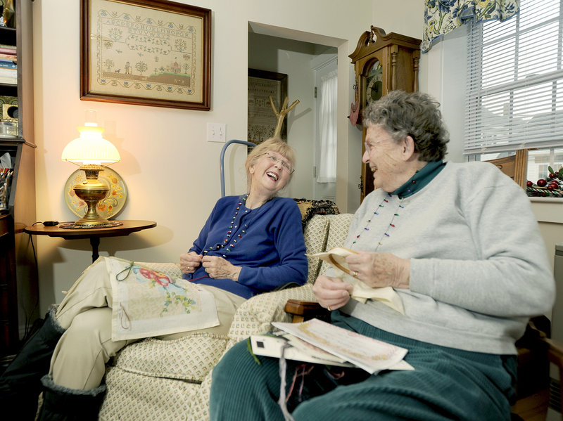Patty Gardner, left, laughs last week with Marian White of Rockport, a Full Circle America volunteer who visits weekly with Gardner in her Rockland home. The visits are part of a monitoring service that allows Gardner, a 77-year-old who suffers from dementia, to live at home alone. The service is less costly than a nursing home or assisted-living options.