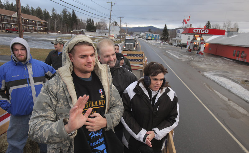 Sgt. Timothy Gilboe waves to well-wishers as he rides in a flatbed truck in his welcome-home parade in Jackman on Thursday. He's accompanied by his parents, Steve and Deanna, and a brother, Ben, left.