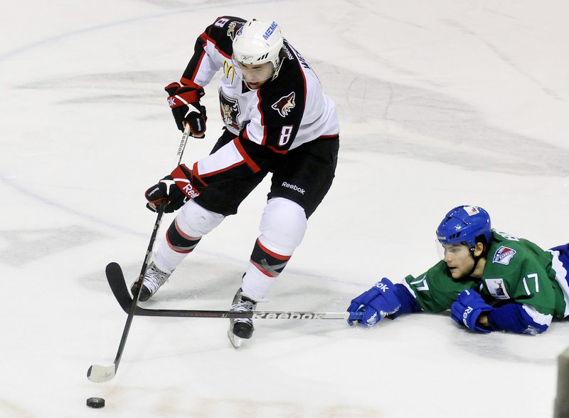 Ryan Bourque, youngest son of former Boston Bruins star Ray Bourque, is sprawling on the ice trying to stop Ethan Werek of the Pirates in Monday's game at the Cumberland County Civic Center. The Pirates rallied to beat the Connecticut Whale 5-4 in overtime.